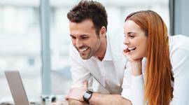 Foto. Homem de cabelo preto com camisa branca e relógio no pulso e mulher de cabelo comprido ruivo e camisa branca estão debruçados sob uma mesa. Ela está com a cabeça apoiada em uma das mãos. Ambos olham para a tela de um computador.