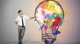 Foto. Homem de óculos, calça social cinza, camisa branca e gravada preta está com a mão encostada em uma lâmpada que é do seu tamanho. A Lãmpada que é um desenho está colorida de várias cores em seu interior.