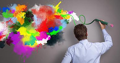 Foto. Homem de camisa azul clara, está de costas e com a mão direita segura uma caneta grande verde com a ponta rosa. Ele está do lado direito da foto e rabisca a parede. Do lado esquerdo observamos a parede que ele já rabiscou com manchas de diversas cores: azul, vermelho, lilás, roxa, amarelo e verde.