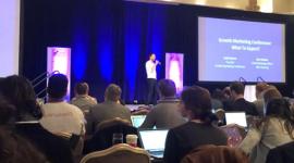 Foto de uma pequena plateia assistindo a uma das palestras da Growth Marketing Conference. No palco o palestrante de pé, com camisa branca e calça preta, segura um microfone.