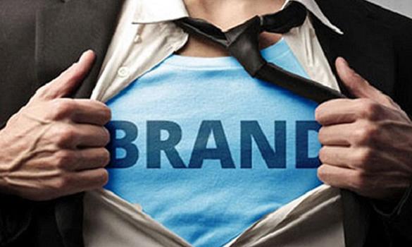 Foto. Homem branco. Só aparece o tronco dele, sem o rosto. Ele veste camiseta azul e com as duas mãos abre a camisa que está por cima dessa camiseta. Na camisa está escrita a palavra Brand.