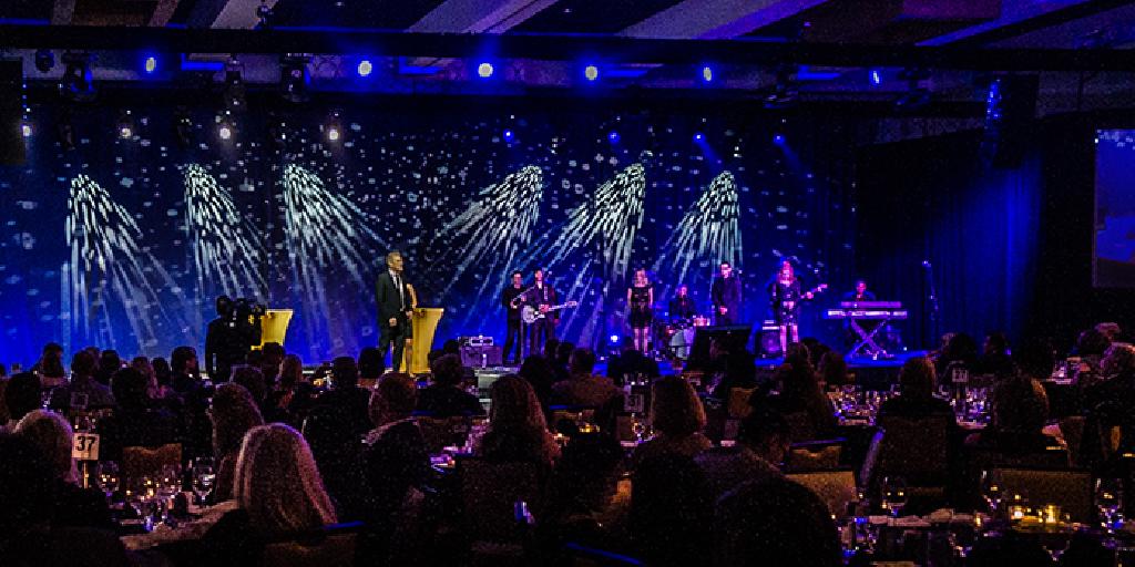 Foto de um evento com muitas pessoas sentadas de costa, olhando para o palco. No palco com fundo azul e alguns efeitos em branco, 7 pessoas estão de pé sendo 5 homens e 2 mulheres. No canto direito da foto tem um homem que toca teclado e está sentado.