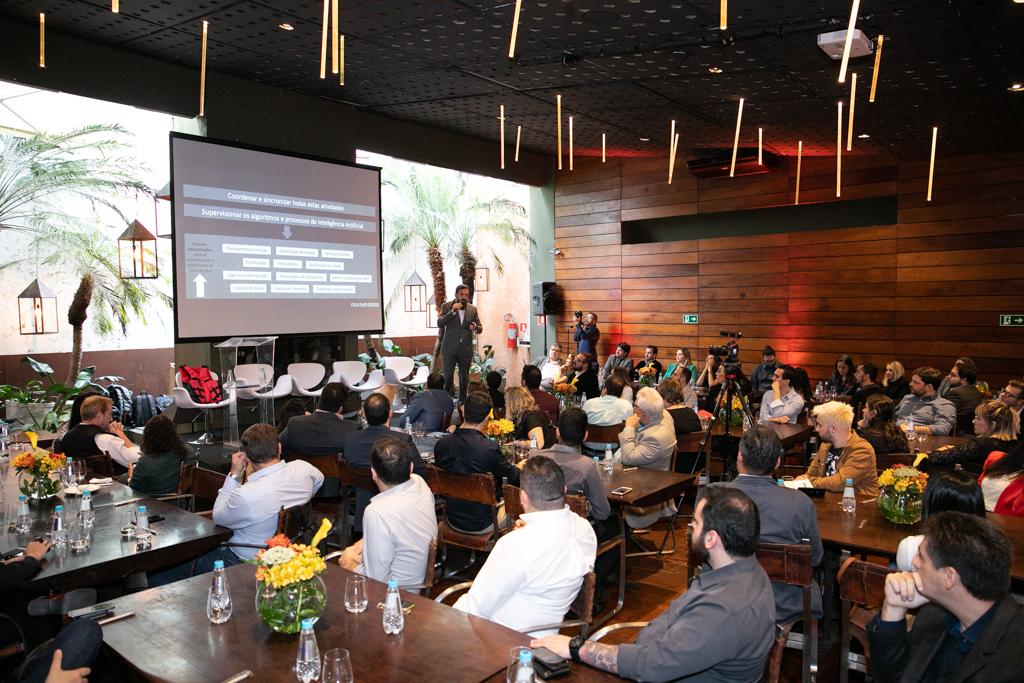 Foto . Mesas e cadeiras de madeira, dispostas em uma sala ampla. Nas cadeiras uma platéia de profissionais assiste à palestra de Marcelo Sousa, da ABRADi. Ele está de terno cinza em cima do palco. Atrás dele uma tela com um slide.