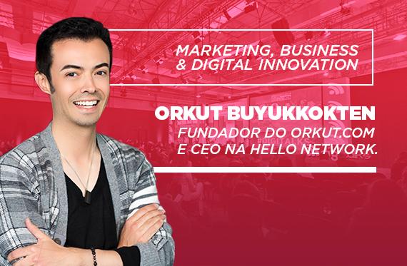 Foto. Criador do Orkut está na lateral esquerda da foto de braços cruzados. Ele veste blusa preta e casaco xadrez. Ao fundo a imagem de um palco e de uma platéia com fundo rosa. Na imagem está escrito: marketing, business &digital. Além de estar escrito o nome do Orkut e o cargo dele.