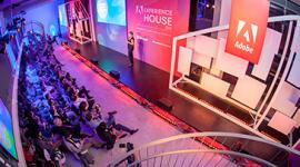 Foto. Evento Adobe Experience House. No palco uma mulher com roupa preta e cabelos loiros curtos, segurando um microfone. Atrás dela um painel vermelho com o nome do evento. Na frente dela, três fileiras de cadeiras com participantes do evento.