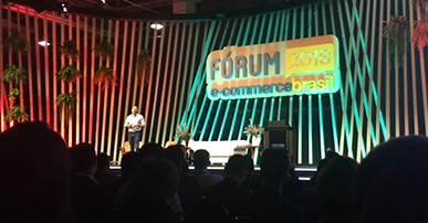 Foto do Alex Szapiro, da Amazon no palco do Fórum E-commerce Brasil. Atrás dele, bem grande, o logotipo do evento em cores amarela e azul e algumas plantas penduradas na estrutura do palco do lado esquerdo. A platéia olhando para ele. Alex está com uma calça cinza e uma camisa branca.