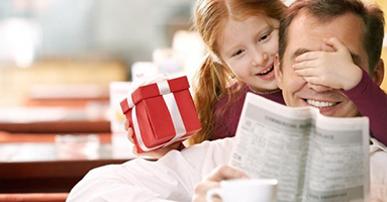 Foto de um pai com camisa branca sentado. Uma xícara de café à sua frente e um jornal em suas mãos. Atrás dele uma menina ruiva que com uma das mãos segura um presente e com a outra tampa os olhos do pai.