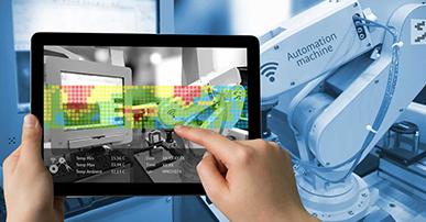 Foto de duas mãos segurando um tablet. Na tela aparece a imagem de uma máquina que está sendo controlada através do tablet. Um pedaço dessa máquina também aparece fora da tela.
