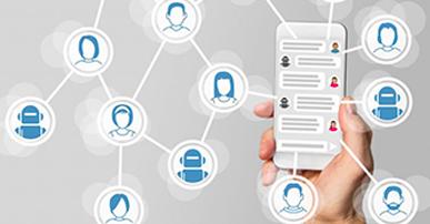 Foto de uma mão segurando um celular. Na tela do celular ícones que identificam espaço para texto com desenho de pessoas. Saindo do dispositivo retas que se conectam com círculos e forma uma espécie de rede. Dentro desses círculos está o desenho da silhueta de pessoas (homens e mulheres) e também robôs.