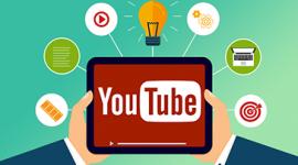 Imagem. Duas mãos seguram um tablet e na tela com fundo vermelho está escrito Youtube. Ao redor do tablet tem alguns ícones: alvo, computador, lâmpada, play, rolo de filme. A cor de fundo da imagem é azul.