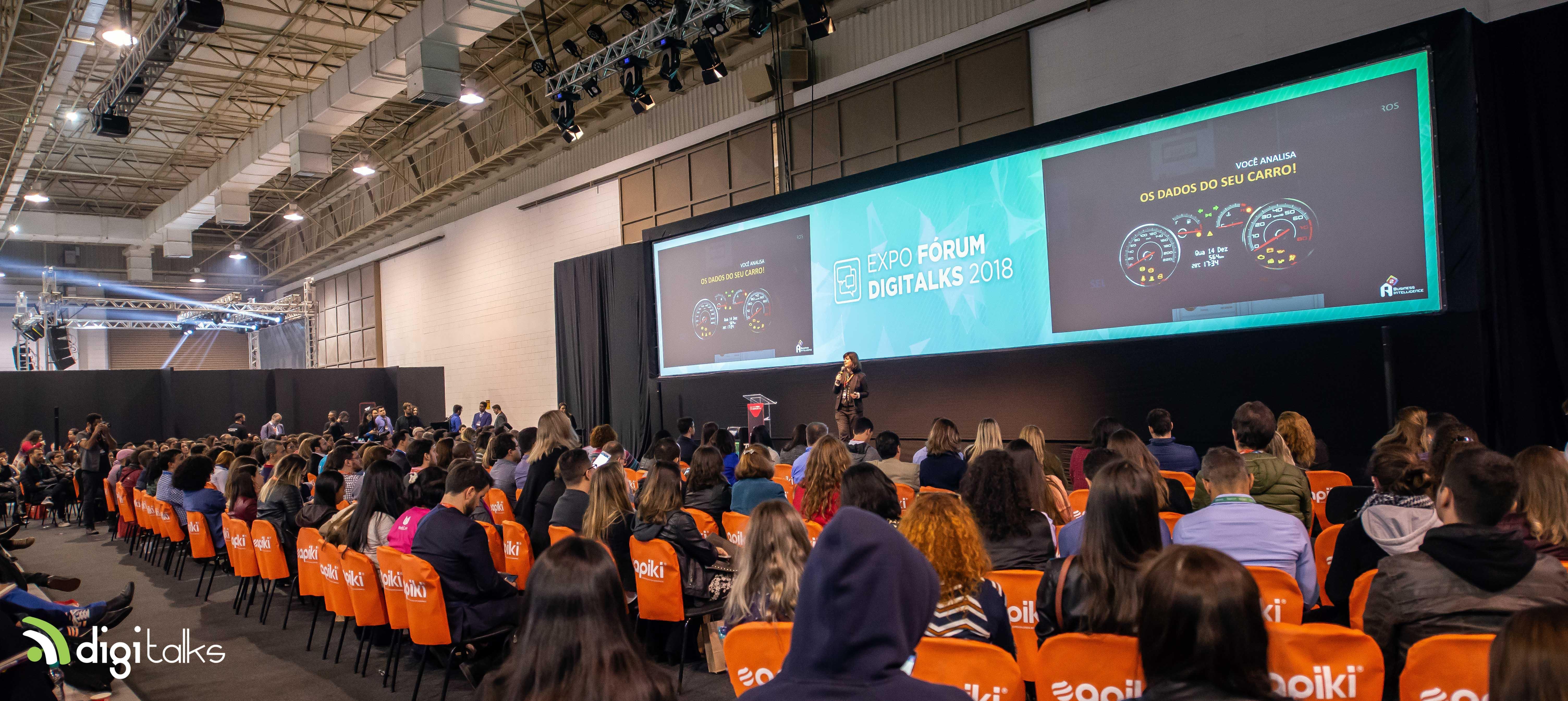 Foto geral do palco Master Seminars. Platéia sentada em cadeiras pretas com capas laranjas e Ariane Maia, no palco. Atrás da Ariane um telão com conteúdo da palestra dela.