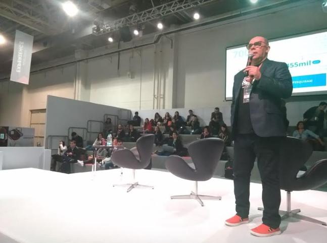 Foto. Homem de terno escuro, está de pé em cima de um palco e com a mão esquerda segura um microfone. Atrás dele uma arquibancada com pessoas e um telão.