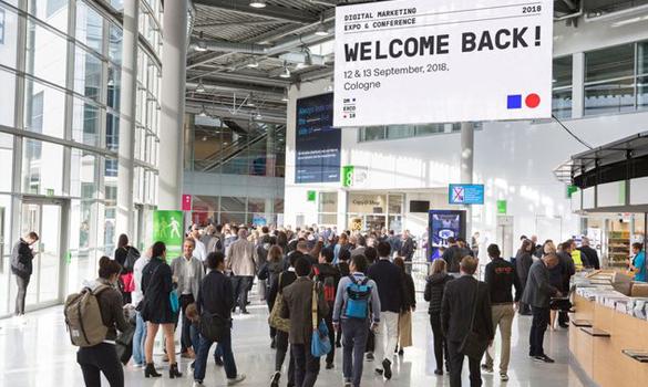 Foto da entrada da Dmexco 2018. Muitas pessoas caminhando em direção à entrada. Do lado direito, uma bancada para o credenciamento das pessoas. Na parte superior da imagem, uma placa escrito welcome back.