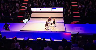 Foto. Três mulheres sentadas em cadeiras brancas que estão em cima de um palco. Na frente e atrás delas duas arquibancadas totalmente preenchidas com pessoas.