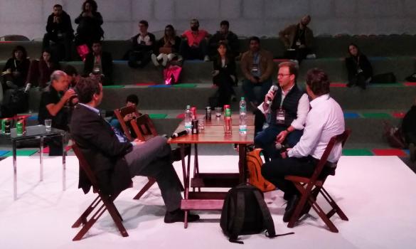Foto. Três homens sentados à mesa que é de madeira e quadrada; Um deles está do lado esquerdo e os outros dois do lado direito. Ao fundouma esécie de arquibancada com três degraus e pessoas sentadas nesses degraus.
