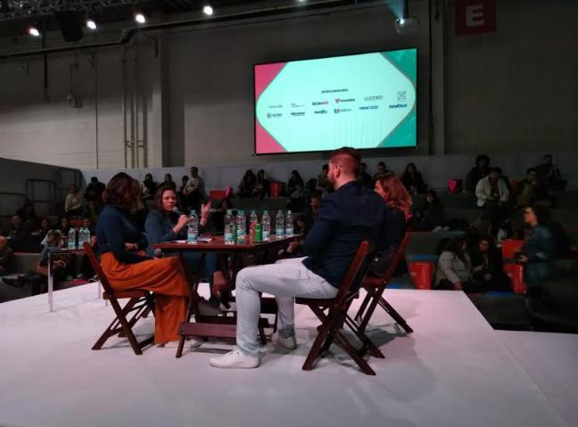 Foto. Quatro pessoas sentadas, sendo três mulheres e um homem, em cadeiras e uma mesa de madeira. A mesa está sobre um palco e atrás deles a platéia os assiste de uma arquibancada pequena. Acima da platéia um telão.