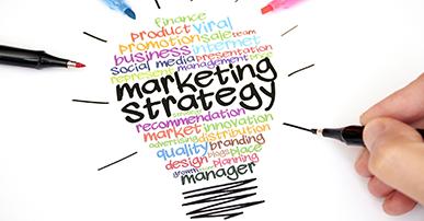 """Imagem. Diversas palavras, de cores variadas, que fazem relação com marketing como: branding, social media, innovation, agrupadas formando o desenho de uma lâmpada. As palavras """"marketing Strategy"""" no centro do desenho em destaque. Em volta da lâmpada, um pedaço de uma mão que segura um caneta e complementa o desenho. Em volta da lâmpada também, mais três canetas de cor preta, azul e rosa que apontam para essa lâmpada."""