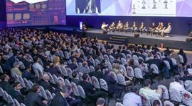 Foto. 10 pessoas sentadas em cadeiras no palco de um evento. Em primeiro plano a platéia com mais de 12 fileiras de cadeiras e pessoas sentadas nelas. Atrás do palco, um painel lilás.