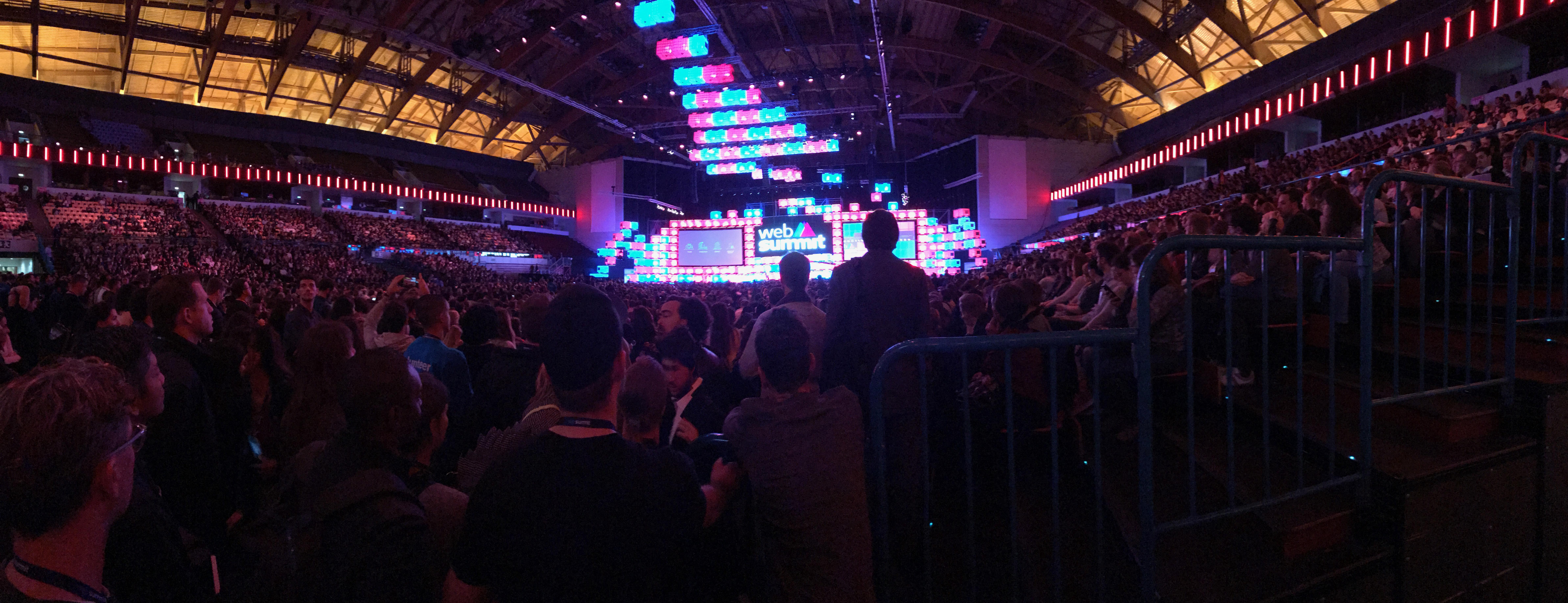 Foto de uma arena, repleta de pessoas sentadas e em pé. Ao fundo, as luzes de palco em rosa e azul.