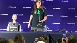 Foto. No palco, atrás de uma bancada preta, estão a robô Sophia e o Ben, seu criador. Ele está de camiseta preta, calça jeans e chapéu e de pé. Ela está sentada, só vemos o tronco. Tem traços bem femininos e é careca. Na frente deles uma pequena platéia de jornalistas os observa.