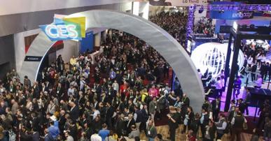 Foto do evento CES 2019. Um acro cinza com o nome do evento escrito ocupa quase toda a imagem. Em baixo do arco várias pessoas conversando.