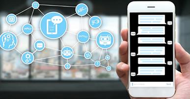 Foto. Mão segurando um celular que na tela tem mensagens de texto. Ao fundo uma janela e alguns ícones em azul claro. Entre os ícones temos: a cabeça de um robô, de um humano, ferramentas, ponto de interrogação e etc.