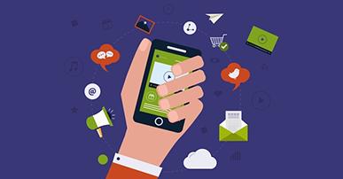Imagem. Mão segurando um celular. Ao redor da mão, a imagem de alguns ícones como: nuvem, envelope, carrinho de mercado, alto-falante, balão indicando fala e etc. O fundo da imagem é roxo.
