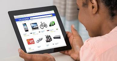 Foto. Mulher negra, vestindo blusa rosa. Ela segura um tablet na mão. Na tela do tablet está aberta uma página de e-commerce.