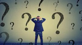Imagem. Homem de terno azul olha para uma parede e está com as mãos na cabeça. Na parede o desenho de diversos pontos de interrogação.