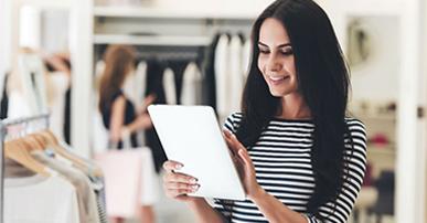 Foto. Mulher magra de cabelos pretos lisos e compridos, usa blusa listrada e está segurando um tablet. Ela está perto de uma arara com roupas e atrás dela uma mulher com sacolas olhando outras roupas. Ambas estão dentro de uma loja.