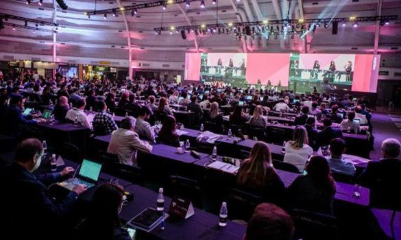 Imagem: palco com iluminação e três pessoas nele, público com muitas pessoas em mesas enfileiradas assistindo.