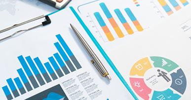 Imagem: gráficos em barra e circular coloridos com uma caneta prata entre eles.
