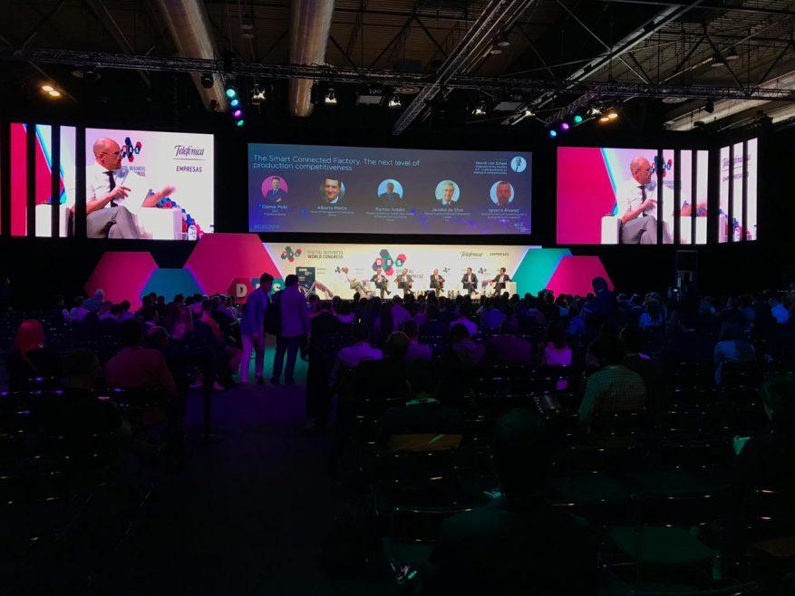 Foto: Grupo de pessoas assistindo uma palestra em frente à um palco com telão.