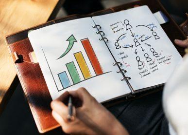 Foto: pessoa segurando uma agenda cm um gráfico positivo.