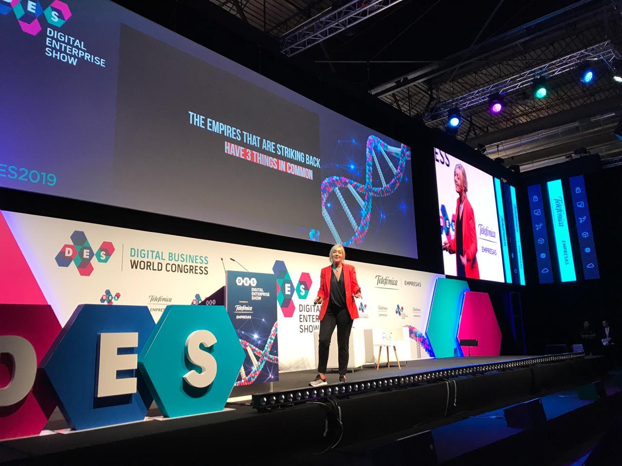 Foto. Marina Specht veste calsa e blusa preta e blazer vermelho. Ela está de pé no palco do DES Madrid 2019. Atrás dela um grande telão e ao lado o logo do DES.