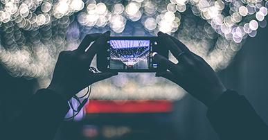 Foto: mãos segurando um celular e tirando uma foto.