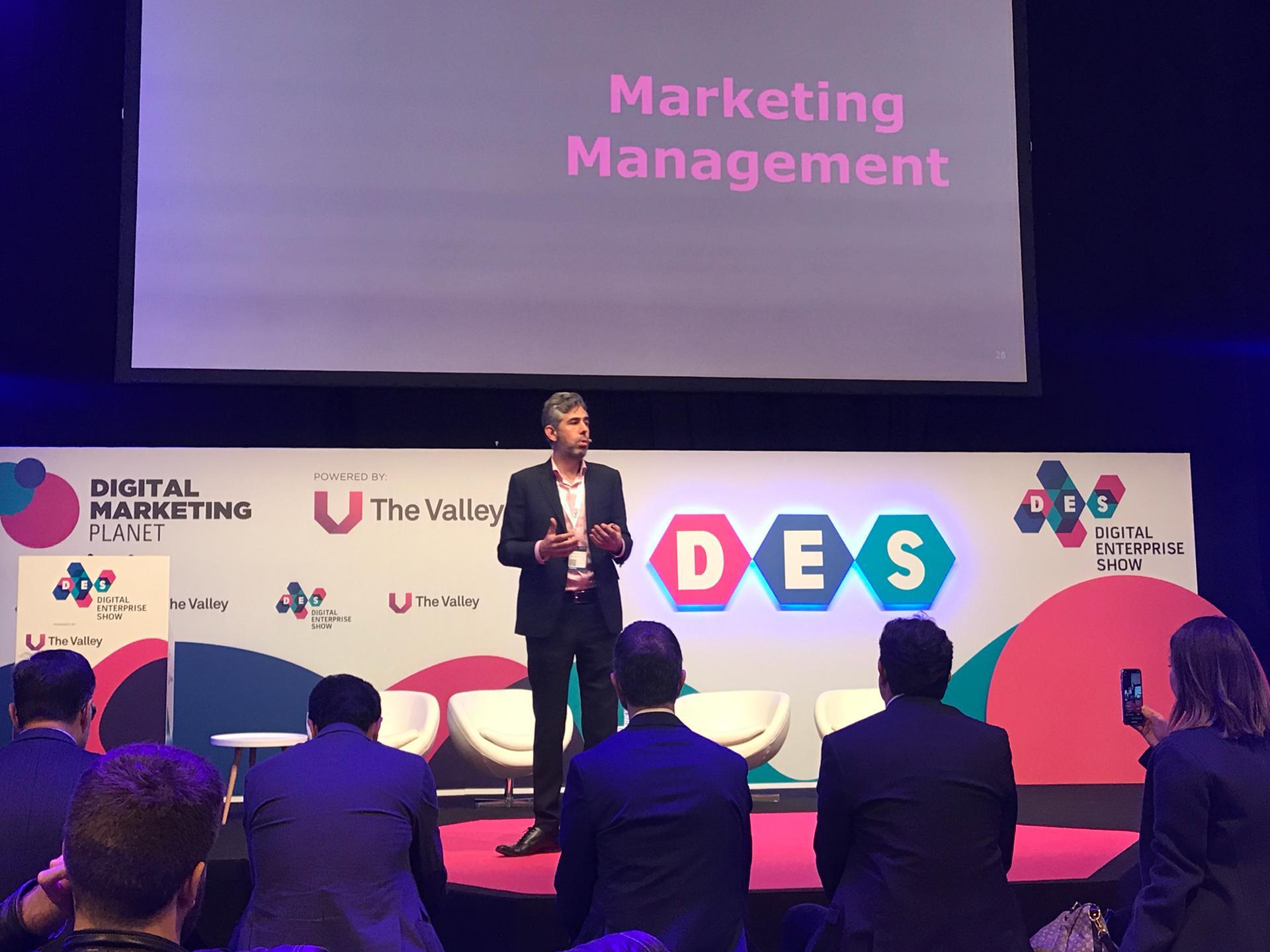 Foto. Nino Carvalho, usa calça e blazer escuros e está em cima de um palco. Atrás dele, 4 cadeiras brancas e 1 banner do DES Madrid 20119. Na platéia algumas pessoas assistindo a palestra.