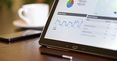 Foto: tablet em cima na mesa com gráficos na tela e uma caneta ao lado.