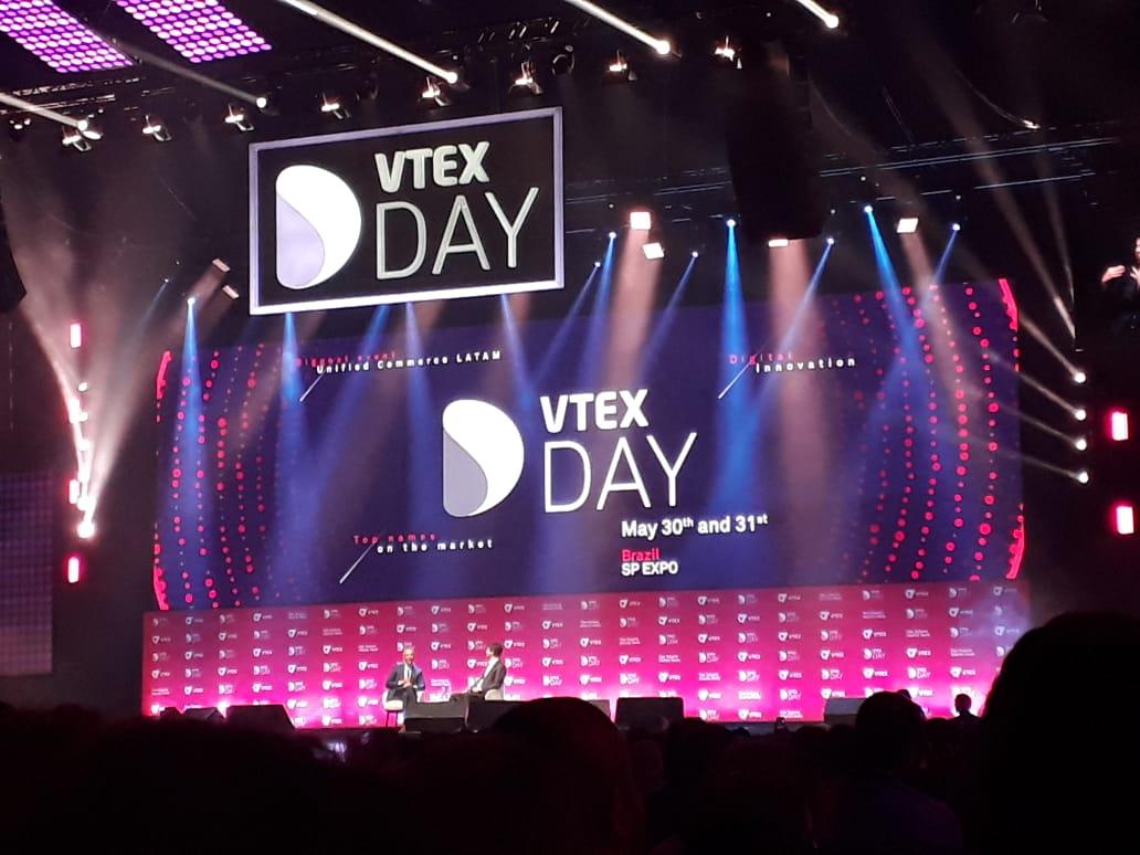 Foto. Palco do vtexday com letreiro branco e fundo roxo. No palco Obama e o CEo da Vtex.