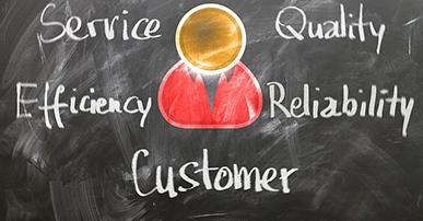 Imagem: lousa com um bonequinho desenhado e as palavras customer, service, efficiency, quality e reliability. consumidor.