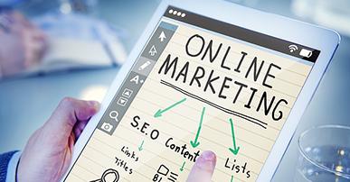 """Imagem: mãos segurando um tablet com a palavras """"marketing online""""."""