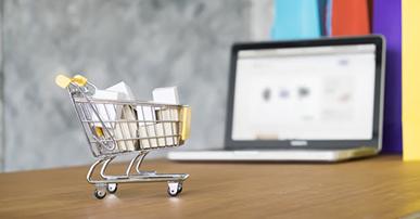 Imagem: notebook aberto com um mini carrinho de compras. Experiências de marca.