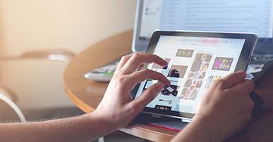 Imagem: mãos mexendo em um tablet que remete ao mobile.