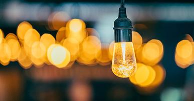 Imagem: lâmpada acessa com fundo desfocado. AI-Powered Marketer.