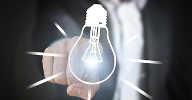 Imagem: homem de terno apontando na direção do desenho de uma lâmpada. Economia Digital