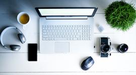 Imagem: computador com café e planta.