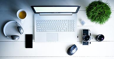 Imagem: computador com café e planta. Expo Fórum Digitalks.