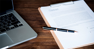 Imagem: computador e caderno em cima da mesa.