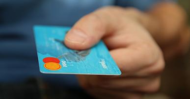 Imagem: mão segurando um cartão de crédito azul.
