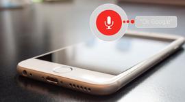 """Imagem: Celular em cima da mesa com um balão de conversa e as palavras """"ok Google""""."""